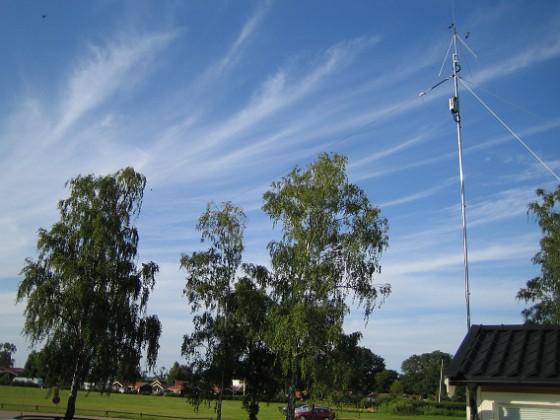 Norra antennmasten Här finns avstämningsenheten till min longwire-antenn, samt min discone för VHF/UHF. Här bör man även kunna se själva antenntråden som hänger mellan masten och björken längst till vänster i bild. 2009-07-17 IMG_0186 Granudden Färjestaden Öland